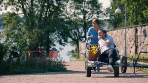 Maria Sundblom Lindberg skuffar Pelle heikkilä i kärra på ön Lonnan en solig sommardag.