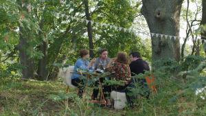 Ett sällskap på fyra personer kring ett festbord uppdukat i en skogsdunge med banderoller.