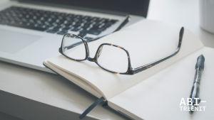 tietokone, vihko ja silmälasit pöydällä