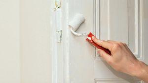 Henkilö maalaa telalla kaapin ovea valkoiseksi.