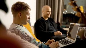 kaksi iloista miestä työskentelevät työpaikan sohvalla läppärien kanssa