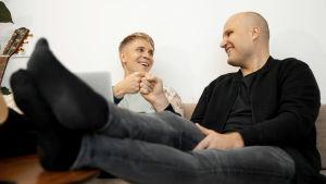 kaksi nuorta miestä istuu työpaikan sohvalla ja iloitsee työn saavutuksista