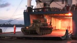 Tankki ajamassa laivan ruumaan tai sieltä pois.