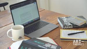 läppäri, kirjoja, kahvikuppi, muistiinpanovälineet