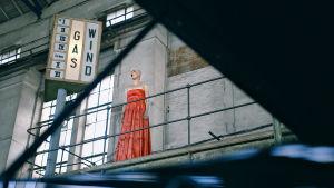 Nainen laulamassa jonkinlaisessa teollisessa maisemassa