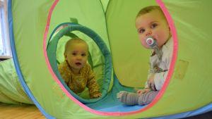 Två babysar sitter i en grön leksakstunnel och kikar ut genom ingångshålet.