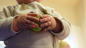 Två babyhänder som håller i en boll.