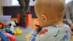 En ettåring fotad bakifrån, hen håller i en plastleksak.
