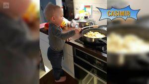 En liten pojke som heter Casimir står på en pall vid spisen och hjälper till med matlagningen