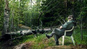 Mies istuu muovituolilla keskellä metsää.