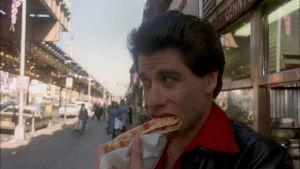 Tony (John Travolta) syö pizzapalaa kadulla elokuvassa Lauantai-illan huumaa