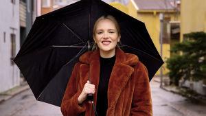 Artisti Titta Hakala seisoo kadulla mustan sateenvarjon alla. Hän katsoo kameraan ja hymyilee ruskea tekoturkis yllään.