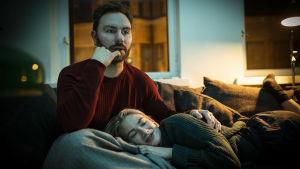 Mies ja nainen katsovat televisiota. Nainen makaa miehen sylissä, mies näyttää keskittyneeltä.