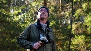 Kaj-Ove Pettersson i skogen tittar upp mot trädkornorna, har en kikare i handen..