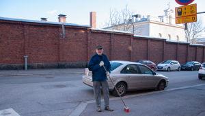 talonmies Kalevi Korhonen kadulla harjan kanssa