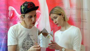 Teoskuvassa Kim Modig ja Heidi M Wee pitelevät ihmetellen käsissään hopeista kruunua