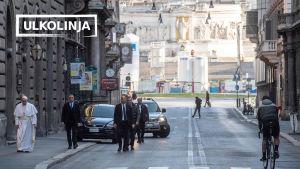 Paavi Franciscus kävelee  Roomassa autioituneella kadulla turvamiesten kanssa.