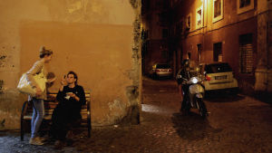 Mies ja nainen keskustelevat kadun kulmassa, skootteri ajaa heidän vieressään. On ilta.