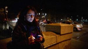 Nainen iltahämärässä kännykkä kädessään.