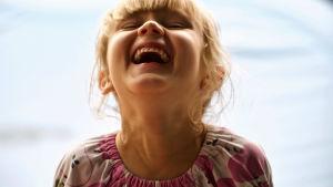 Pieni tyttö nauraa pää taakse kallistuneena.