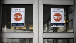 Vieraat kieltävät kyltit Pohjois-Karjalan keskussairaalan ulko-ovissa.