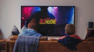 Lapset katsovat sohvalla Yle Olohuone -ohjelmaa.
