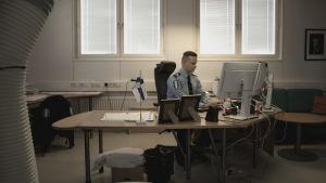 Polis som sitter vid ett skrivbord framför en dator.