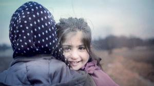 Lapsi halaa aikuista, katsoo kameraan ja hymyilee.