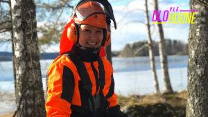 Arja Koriseva hymyilee kameralle metsämaisemassa metsurivarusteissa ja raivaussaha käsissään.
