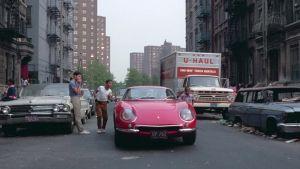 Punainen Ferrari ajaa kadulla New Yorkissa, pojat juoksevat auton rinnalla.