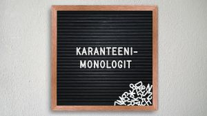 Karanteenimonologit-lause kirjoitettu valkoisin irtokirjaimin mustalle ilmoitustaululle.