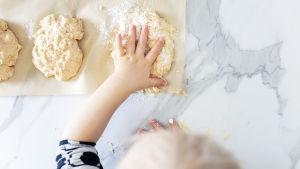 Pienen lapsen käsi painelee sämpylää uunipellille.