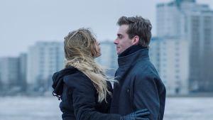 Sofia Karppi (Pihla Viitala) ja Sakari Nurmi (Lauri Tilkanen) syleilevät harmaassa talvisessa säässä. Taustalla Merihaan betonitaloja.