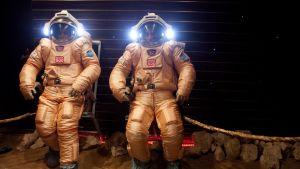 Kaksi miestä avaruuspuvuissa.
