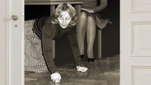 Seela Sella on palvelustyttö ja rouva Ritva Ahonen. Palvelustyttö kuuraa lattiaa.
