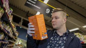 Eerik Peltomäki tutkii puuropaketin tuotetietoja ruokakaupassa.