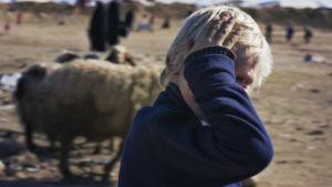 Vaalea pikkupoika katsoo kameraan peittäen kädellä kasvonsa.