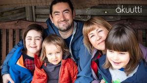Vanhemmat Anna ja Cagri Akgul istuvat puutarhakeinussa lastensa Akselin, Alvarin ja Einarin kanssa.