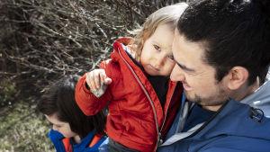 2,5-vuotias Alvar on isänsä Cagrin sylissä ja katsoo kameraan.