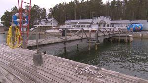Verkans gästhamn i Korpo, en grå byggnad med bryggor i förgrunden.