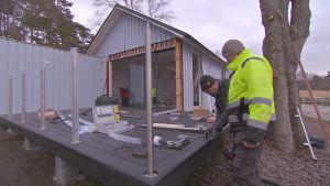 Två män i byggoveraller står framåtböjda vid ett husbygge.