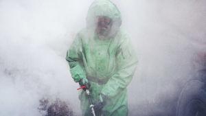 Valeanvihreään suoja-asuun pukeutunut sotilas desinfioi koronavirusepidempian aikaan. Hänen ympärillään on runsaasti höyryä.