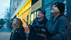 Kolme hakkeria seisovat kadulla tietokone kädessä.