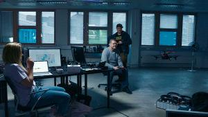 Kolme hakkeria kokeilevat lennättää dronea toimistossaan.