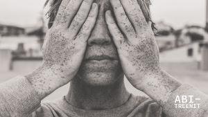 nuori mies kädet silmillä
