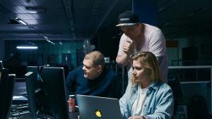 Kolme tyyppiä istuvat tietokoneen ääressä.