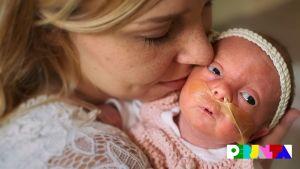 Äiti Saara Tolonen pitelee hellästi sylissään pientä Hilda-vauvaa, jolla happiviikset.