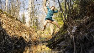 Nora Gullmets hoppar över en bäck.