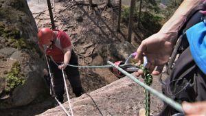 Elisabeth Morney firar ner sig med rep längs med bergsklippa i Repovesi nationalpark.