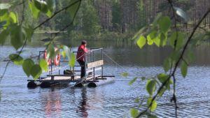 Elisabeth Morney drar sig över en sjö med en vajerflotte.